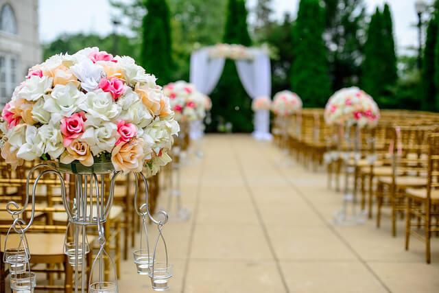 Kvetinová svadobná výzdoba pomedzi stoličky pre svadobných hostí